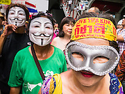 "02 JUNE 2013 - BANGKOK, THAILAND:  An anti-government protester wearing a We Love the King headband, marches with other anti-government protesters. The so called White Mask protesters are strong supporters of the Thai monarchy. About 300 people wearing the Guy Fawkes mask popularized by the movie ""V for Vendetta"" and Anonymous, the hackers' group, marched through central Bangkok Sunday demanding the resignation of Prime Minister Yingluck Shinawatra. They claim that Yingluck is acting as a puppet for her brother, former Prime Minister Thaksin Shinawatra, who was deposed by a military coup in 2006 and now lives in exile in Dubai.    PHOTO BY JACK KURTZ"