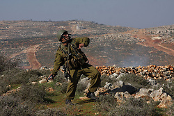 An Israeli soldier fires tear gas in attempt to subdue the Palestinian protestors (not seen) during clashes near the West Bank village of Qusra, near Nablus city, Israel, January 1, 2013. Photo by Imago / i-Images...UK ONLY