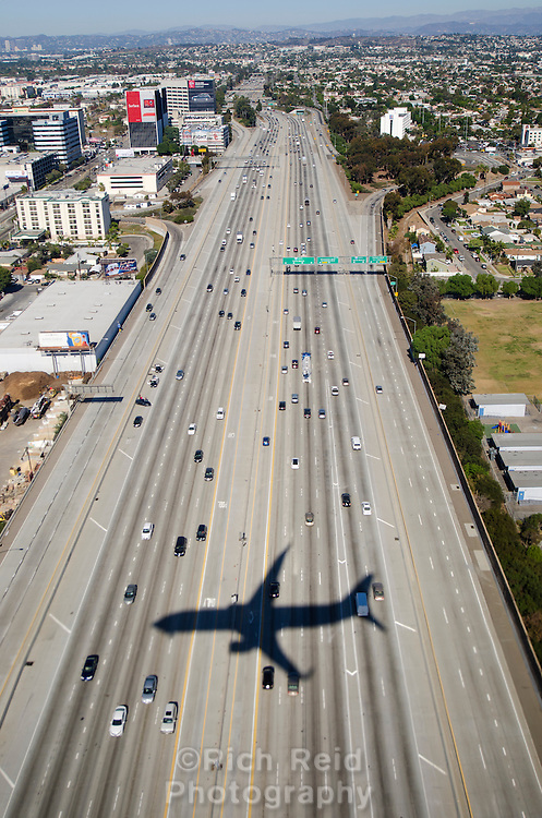 Aerial view of a jet's shadow on Interstate 405 on a commercial flight landing at Los Angeles Airport, California.
