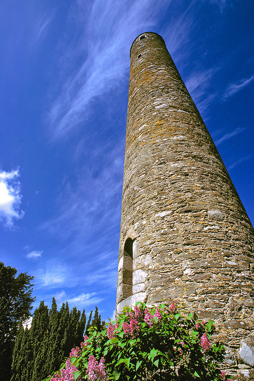 A tall, round tower reaches to the sky in Glendalough, County Wicklow, Ireland.