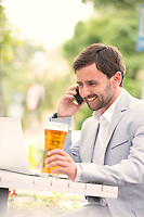 Happy businessman using mobile phone and laptop while holding beer glass at outdoor restaurant
