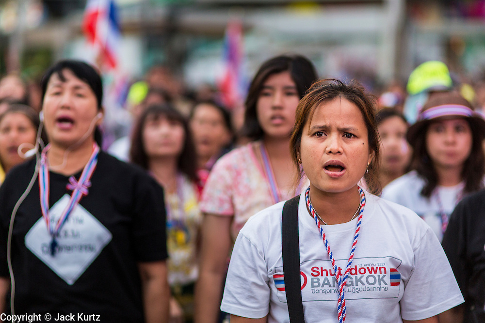 24 JANUARY 2014 - BANGKOK, THAILAND: An anti-government protestors sing the Thai national anthem at the Pathum Wan Shutdown Bangkok protest site. Shutdown Bangkok has been going for 12 days with no resolution in sight. Suthep Thaugsuban, the leader of the anti-government protests and the People's Democratic Reform Committee (PDRC), the umbrella organization of the protests,  is still demanding the caretaker government of Prime Minister Yingluck Shinawatra resign, the PM says she won't resign and intends to go ahead with the election.    PHOTO BY JACK KURTZ