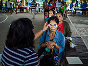 "22 JANUARY 2018 - GUINOBATAN, ALBAY, PHILIPPINES: A woman in an evacuation center in Guinobatan gets her eyes checked during a clinic at the shelter. Several communities in Guinobatan were hit ash falls from the eruptions of the Mayon volcano and many people wore face masks to protect themselves from the ash. There were a series of eruptions on the Mayon volcano near Legazpi Monday. The eruptions started Sunday night and continued through the day. At about midday the volcano sent a plume of ash and smoke towering over Camalig, the largest municipality near the volcano. The Philippine Institute of Volcanology and Seismology (PHIVOLCS) extended the six kilometer danger zone to eight kilometers and raised the alert level from three to four. This is the first time the alert level has been at four since 2009. A level four alert means a ""Hazardous Eruption is Imminent"" and there is ""intense unrest"" in the volcano. The Mayon volcano is the most active volcano in the Philippines. Sunday and Monday's eruptions caused ash falls in several communities but there were no known injuries.    PHOTO BY JACK KURTZ"