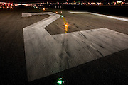 "A wide night view looking down on the rubber-stained of runway 27R at Heathrow Airport. During a time-exposure and partially-lit by the headlights and spotlights of an airfield emergency vehicle, we see the giant numbers 27 that landing pilots will see from a mile away as they descend towards the airport's threshold. The numbers relate to the compass bearing that the line of the runway takes: In this case 270 degrees from north and has a parallel southern twin. Across the number two we also see a set of taxiway lights that help the steering pilot navigate across the airfield and line-up on the departing runway. .From writer Alain de Botton's book project ""A Week at the Airport: A Heathrow Diary"" (2009). ."