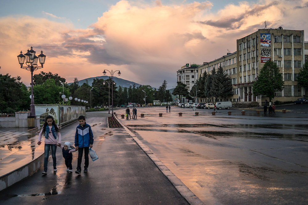 People walk in Renaissance Square in the city center following an evening rain storm on Sunday, May 8, 2016 in Stepanakert, Nagorno-Karabakh.