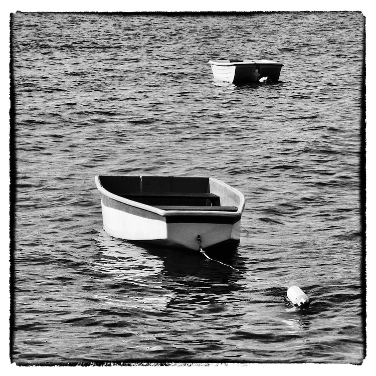 Vintage dinghies at the Connecticut shore in Niantic. Two wooden rowboats moored just offshore, a classic New England scene. Part of a new series of black and white nautical images I'm working on.