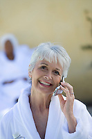 Portrait of senior woman in bathrobe using mobile phone