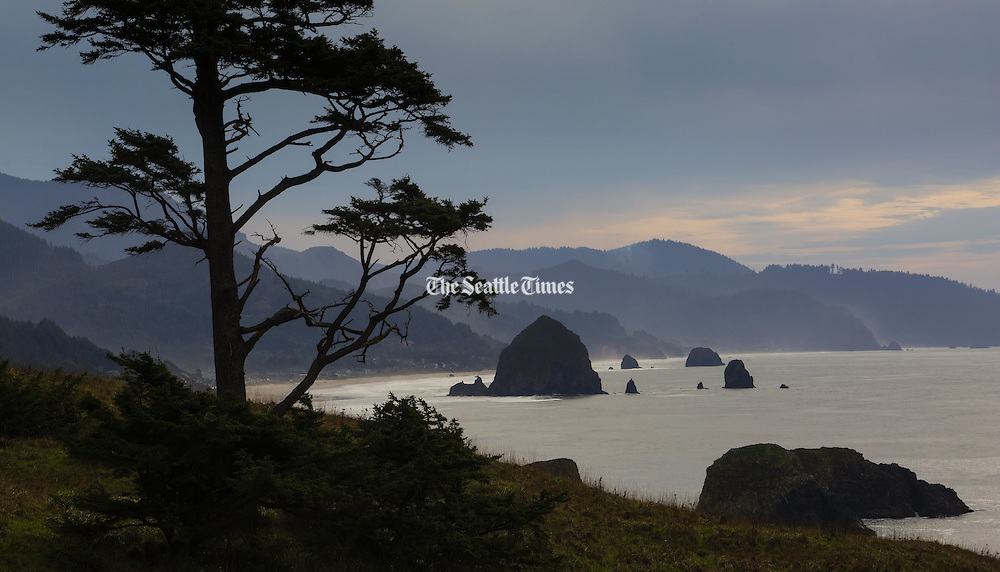 Haystack Rock (big rock in water at middle left) and the beach at Cannon Beach are seen  from Ecola State Park in Cannon Beach, OR.<br />