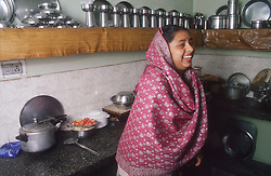 Woman standing in kitchen wearing traditional dress laughing,