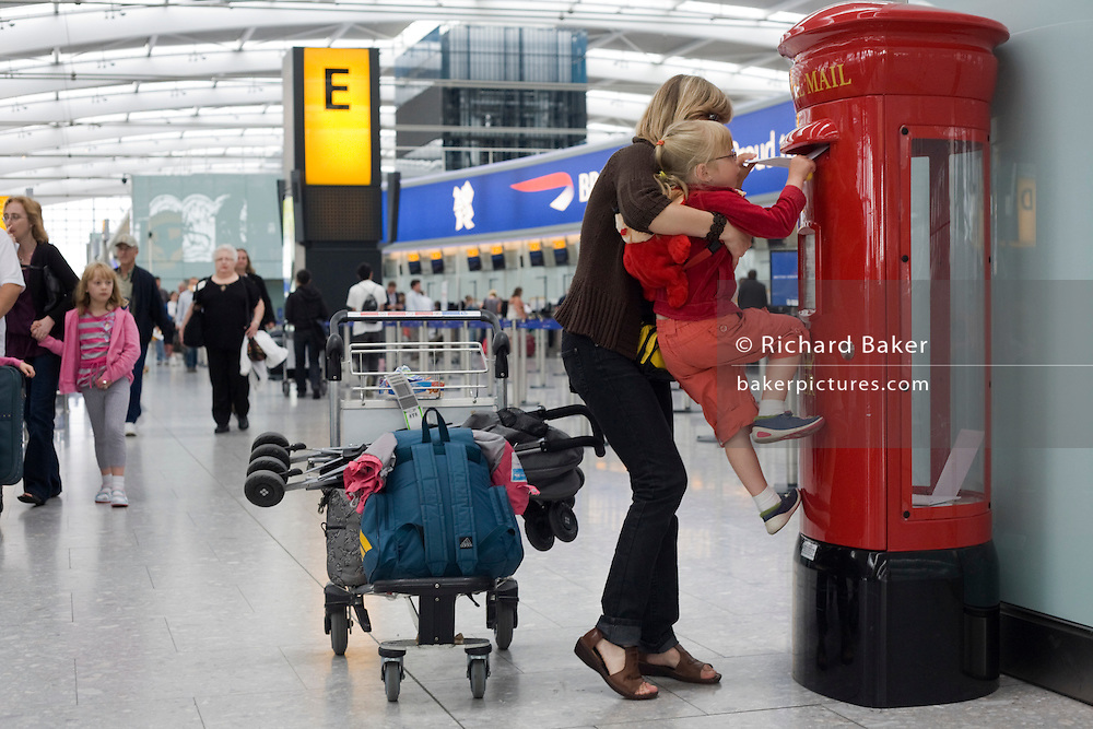 "A young mother holds up her daughter to insert a letter into a post box at Heathrow Airport's Terminal 5. The girl half-climbs up the red pillar box and tries to get the postage item into the narrow slot which is an even tighter fit because of security considerations - avoiding larger and potentially dangerous packages from entering the airport's postal system. In the background we see the bustle of a departures concourse where British Airways passengers walk past after having checked-in at BA's hub terminal. At a cost of £4.3 billion, Terminal 5 has the capacity to serve around 30 million passengers a year. From writer Alain de Botton's book project ""A Week at the Airport: A Heathrow Diary"" (2009). .."