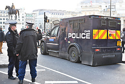 © Licensed to London News Pictures. 23/03/2017. London, UK. Heavily armored police vehicles watch over A vigil held in Trafalgar Square, London, to remember those killed in the Westminster terror attack, the day after a lone terrorist killed 4 people and injured several more, in an attack using a car and a knife. The attacker managed to gain entry to the grounds of the Houses of Parliament, killing one police officer. Photo credit: Ben Cawthra/LNP