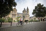 In Roermond passeert een vader met een kind op de fiets de Munsterkerk. De 13e eeuwse kerk is het enige overblijfsel van een abdij voor Cistercienzer nonnen, gesticht in 1218 door Graaf Gerard IV van Gelre. Het is het enige voorbeeld van een kerk in laat-romaanse stijl in Nederland en de kerk siert de ruitenaas van het Nederlandse kaartspel.<br /> <br /> In Roermond a father with a child on the bike passes the Minster Church. The 13th century church is the only remnant of an abbey of Cistercian nuns, founded in 1218 by Count Gerard IV of Gelre. It is the only example of a church in late-Romanesque style in the Netherlands and the ace of diamonds of the Dutch card game adorns the church.