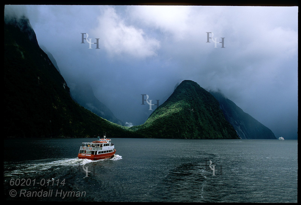 Red tour boat sets off on trip around Milford Sound; Fiordland National Park, New Zealand.