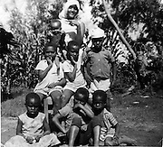 Chidren have their photo taken in the Lindi section of Kibra.  Nubian homesteads were used for farming.  At one time Kibra was a lush village, filled with plantations of banana and maize as well as trees.  (1968)