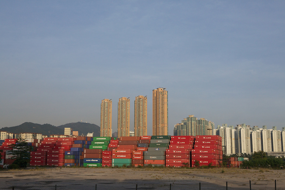 Shipping containers at the dock with human containers in the distance. Taken from inside the Kwai Tsing Container Terminals. Mei Foo are the low white buildings on the left, Manhattan Hill Towers are the four tall buildings in the centre, and Ho Lai Estate is the phalanx on the right.