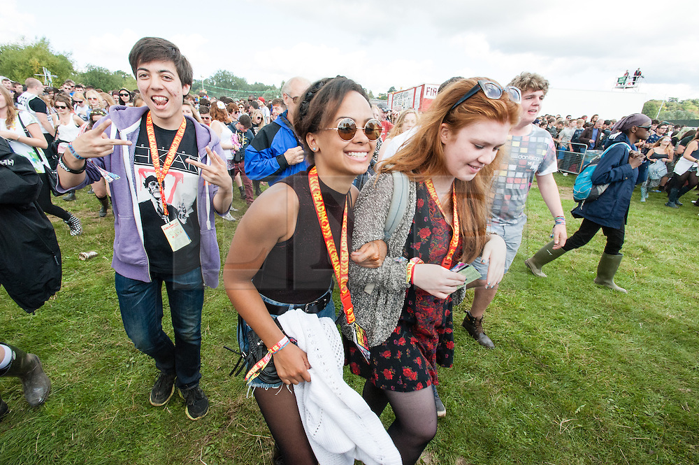 © Licensed to London News Pictures. 22/08/2014. Reading, UK.   Festival goers rush through the gates at Reading Festival 2014 on Friday morning, the opening day, just as the gates open at 11am.  The weather is sunny with light cloud.   Today is expected to remain dry with a 25% risk of showers.  Photo credit : Richard Isaac/LNP