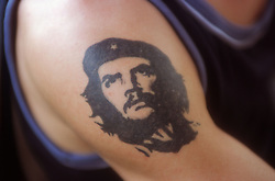 Close up of man's arm with the image of Che Guevara tattooed onto it,