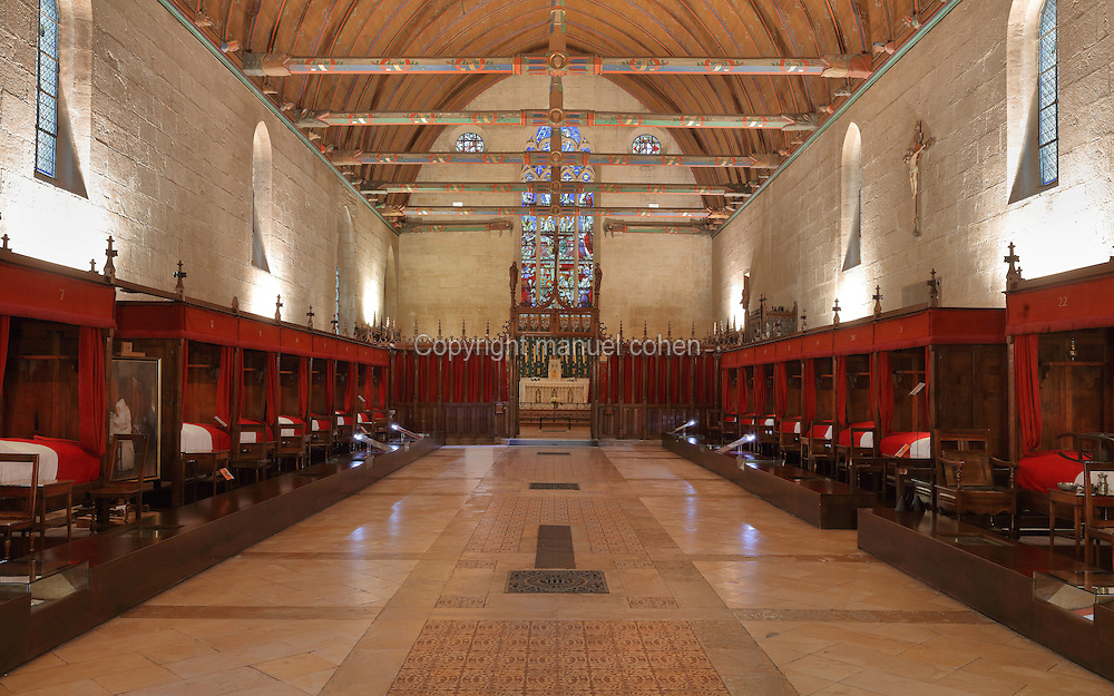 Salle des Povres or Room of the Poor, almost 50m long, with curtained beds for patients and a painted wooden ceiling with dragons' heads and caricatures of local people, and the chapel behind, in Les Hospices de Beaune, or Hotel-Dieu de Beaune, a charitable almshouse and hospital for the poor, built 1443-57 by Flemish architect Jacques Wiscrer, and founded by Nicolas Rolin, chancellor of Burgundy, and his wife Guigone de Salins, in Beaune, Cote d'Or, Burgundy, France. The furniture was restored in 1875 by Maurice Ourdou. The hospital was run by the nuns of the order of Les Soeurs Hospitalieres de Beaune, and remained a hospital until the 1970s. The building now houses the Musee de l'Histoire de la Medecine, or Museum of the History of Medicine, and is listed as a historic monument. Picture by Manuel Cohen