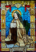 "St. Therese of Lisieux with pictures of the child Jesus and the ""holy face."" Part of stained glass collection depicting life of St. Therese located at Holy Hill Chapel. (Sam Lucero photo)"