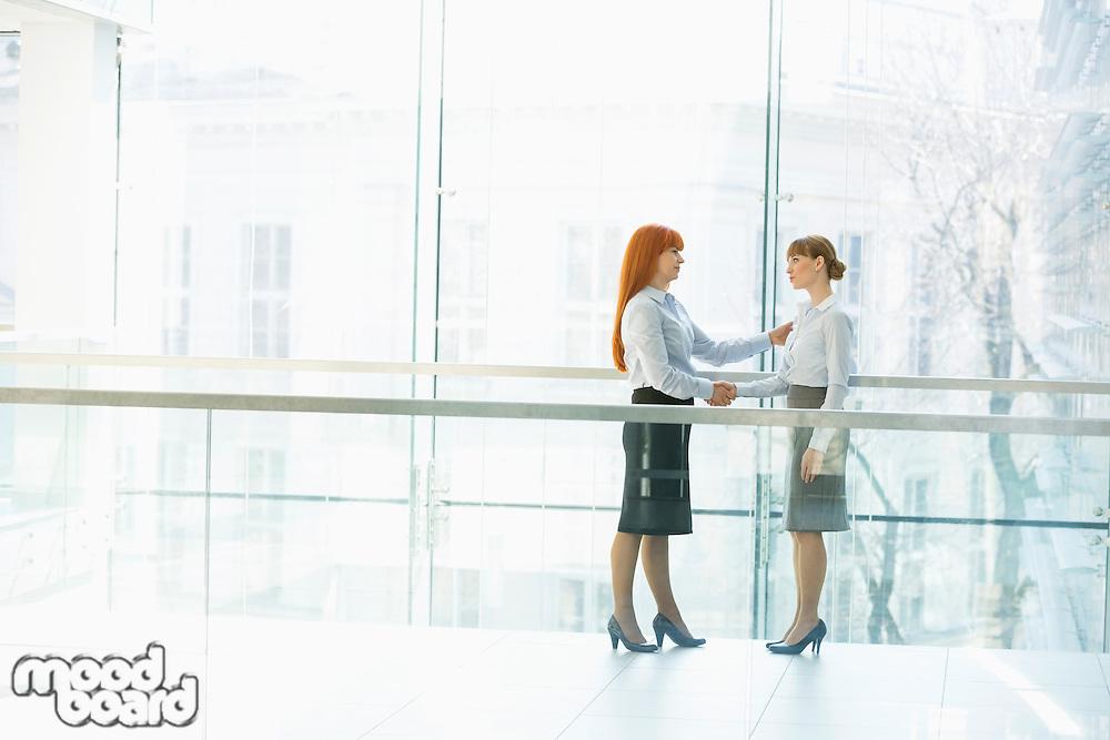 Full-length businesswomen shaking hands in office
