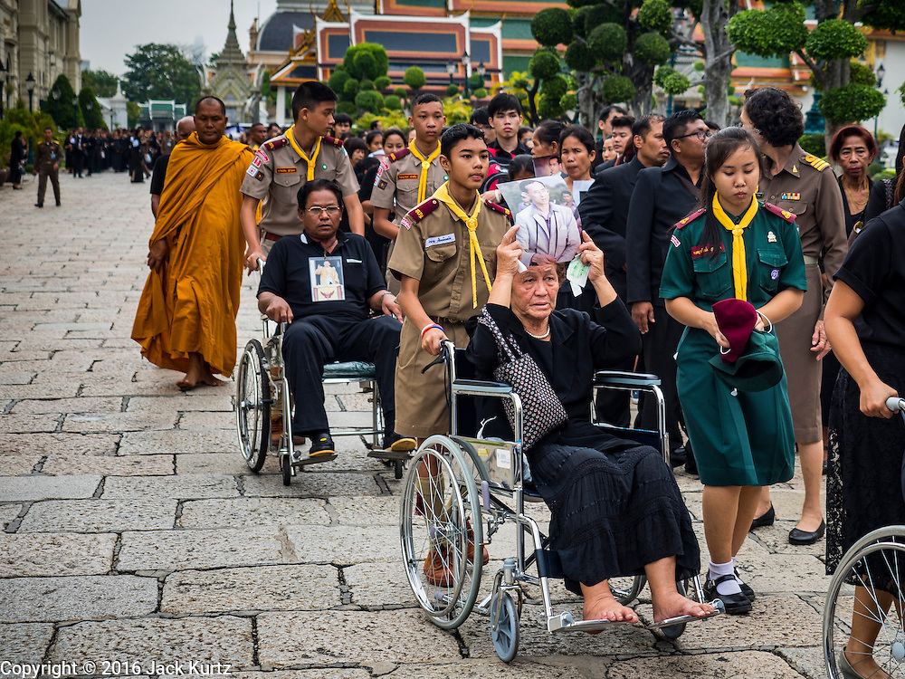 29 OCTOBER 2016 - BANGKOK, THAILAND:  Thai boy scouts help people in wheelchairs go into the Grand Palace to pay homage to the late Thai King. Saturday was the first day Thais could pay homage to the funeral urn of the late Bhumibol Adulyadej, King of Thailand, at Dusit Maha Prasart Throne Hall in the Grand Palace. The Palace said 10,000 people per day would be issued free tickerts to enter the Throne Hall but by late Saturday morning more than 100,000 people were in line and the palace scrapped plans to require mourners to get the free tickets. Traditionally, Thai Kings lay in state in their urns, but King Bhumibol Adulyadej is breaking with tradition. His urn reportedly contains some of his hair, but the King is in a coffin,  not in the urn. The laying in state will continue until at least January 2017 but may be extended.       PHOTO BY JACK KURTZ