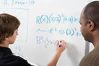 Student writing maths equations on whiteboard with tutor
