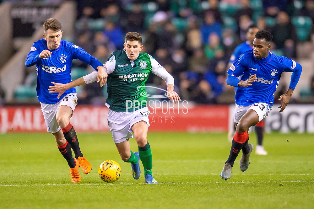 Emerson Hyndman (#20 ) of Hibernian FC runs between Ryan Jack (#8) of Rangers FC (left) and Lassana Coulibaly (#23) of Rangers FC during the Ladbrokes Scottish Premiership match between Hibernian and Rangers at Easter Road, Edinburgh, Scotland on 19 December 2018.