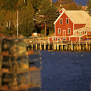 A scenic view of Midcoast Maine from Bailey Island in Harpswell, at sunset. In the foreground are lobster traps.