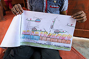 BKCFS centre, Rohingya refugee crisis, Cox's Bazar, Bangladesh. Manjur Ali, (11) from Bolibazar, Maungdaw, Myanmar - uses art to describe what he witnessed in his village in Myanmar. Photograph by David Dare Parker