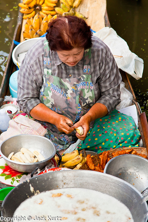 "10 JULY 2011 - DAMNOEN SADUAK, RATCHABURI, THAILAND:  A vendor in the floating market in Damnoen Saduak, Thailand, slices bananas before deep frying them on her boat. The Thai countryside south of Bangkok is crisscrossed with canals, some large enough to accommodate small commercial boats and small barges, some barely large enough for a small canoe. People who live near the canals use them for everything from domestic water to transportation and fishing. Some, like the canals in Amphawa and nearby Damnoensaduak (also spelled Damnoen Saduak) in Rajburi  province (also spelled Ratchaburi) are also relatively famous for their ""floating markets"" where vendors set up their canoes and boats as floating shops.     PHOTO BY JACK KURTZ"