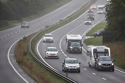 © Licensed to London News Pictures. 04/07/2020. Truro, UK. Caravans and campervans travel on the southbound (right hand side) carriage of the A30 in central Cornwall. Today marks a lift in COVID-19 restrictions, as tens of thousands of tourists are due to arrive in Cornwall over this weekend.  Overnight stays within England are also now allowed. Photo credit : Tom Nicholson/LNP