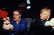 Two excited men playing shoot-em-up arcade games, Sea side, Blackpool, UK, 1998.