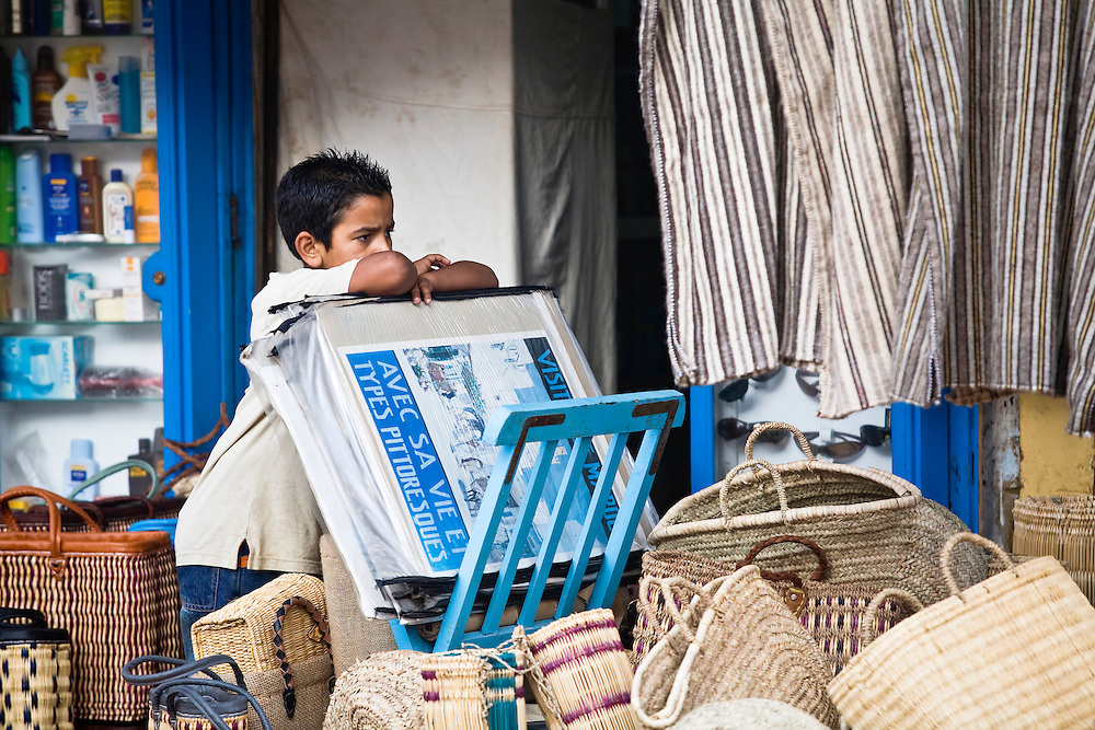 A young boy working at a stall in the narrow streets of Essaouira, Morocco.