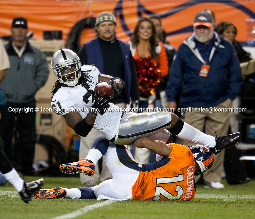 Sept. 23, 2013 - Denver, Colorado, U.S - Raiders CB MIKE JENKINS, top, gets tackled after picking up a fumble during the 2nd. half at Sports Authority Field at Mile High Monday Night. The Broncos beat the Raiders 37-21