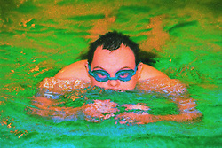 Teenage boy with Downs Syndrome swimming in public swimming pool,