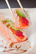 Chopsticks pick up a sushi roll with pink rice paper, tuna, salmon and avocado.