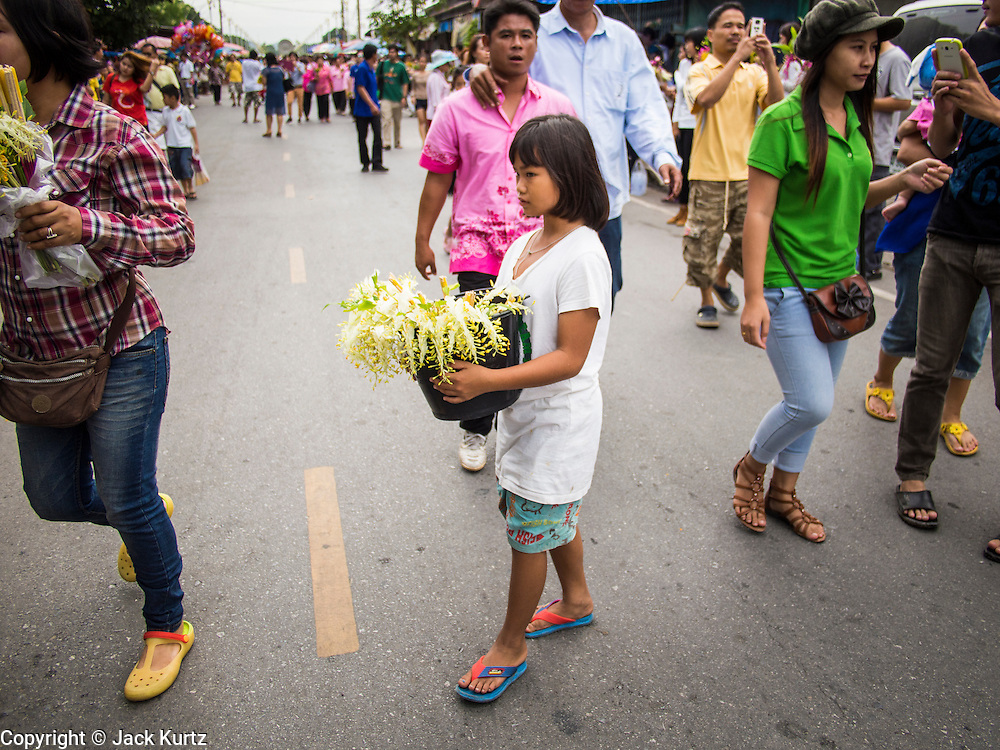 "22 JULY 2013 - PHRA PHUTTHABAT, THAILAND: A girl walks among the crowd selling flowers during the Tak Bat Dok Mai at Wat Phra Phutthabat in Saraburi province of Thailand, Monday, July 22. Wat Phra Phutthabat is famous for the way it marks the beginning of Vassa, the three-month annual retreat observed by Theravada monks and nuns. The temple is highly revered in Thailand because it houses a footstep of the Buddha. On the first day of Vassa (or Buddhist Lent) people come to the temple to ""make merit"" and present the monks there with dancing lady ginger flowers, which only bloom in the weeks leading up Vassa. They also present monks with candles and wash their feet. During Vassa, monks and nuns remain inside monasteries and temple grounds, devoting their time to intensive meditation and study. Laypeople support the monastic sangha by bringing food, candles and other offerings to temples. Laypeople also often observe Vassa by giving up something, such as smoking or eating meat. For this reason, westerners sometimes call Vassa the ""Buddhist Lent.""     PHOTO BY JACK KURTZ"