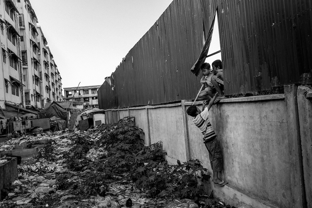 Children jump through a gap in the fence that separates Borei Keila from neighbouring vacant lots. The community of Borei Keila in Phnom Penh was once home to hundreds of families before land developer Phanimex bought the property rights to the area and forcefully evicted the residents who refused to accept their compensation package. Those who remained were forced to squat in the remains of the buildings, living in slum-like conditions and without access to plumbing or public electiricity.