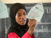Teacher Mafunda Mohammed is teaching a class full of primary school children at Saateni nursery school, Zanzibar. Teacher Mafunda has been working along side VSO volunteer teacher, Daphne Sharp.
