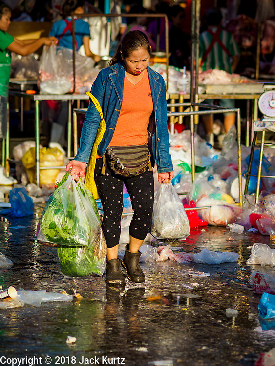 "04 DECEMBER 2018 - BANGKOK, THAILAND:  A shopper carrying her purchases in single use plastic bags walks through Khlong Toei market. The issue of plastic waste became a public one in early June when a whale in Thai waters died after ingesting 18 pounds of plastic. In a recent report, Ocean Conservancy claimed that Thailand, China, Indonesia, the Philippines, and Vietnam were responsible for as much as 60 percent of the plastic waste in the world's oceans. Khlong Toey (also called Khlong Toei) Market is one of the largest ""wet markets"" in Thailand. December 4 was supposed to be a plastic free day in Bangkok but many market venders continued to use plastic.     PHOTO BY JACK KURTZ"