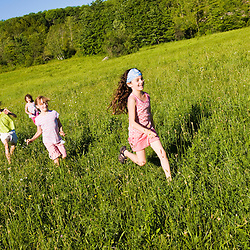 Young girls explore a field in Sabins Pasutre in Montpelier, Vermont.