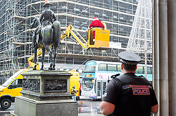 A police officer for Police Scotland waits for a quiet word with Ricky McConnell who dressed as Santa and waved at passeres by from the Duke of Wellington on the statue in Royal Exchange Square Glasgow<br />