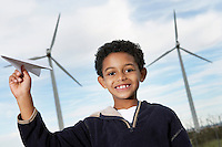 Boy (7-9) playing with paper plane at wind farm, portrait