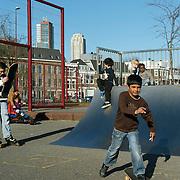 Nederland Rotterdam 7 maart 20110 20110307 Achterstandswijk Katendrecht. Skateplein in de wijk, kinderen skaten, spelen. Op de achtgrond een deel van de rotterdamse skyline: Hoogbouw Montevideo en New Orleans.  Deelgemeente Feijenoord,.Oud Zuid, omvat 4 probleemwijken die waarvan 1 Katendrecht. , publiek domein, publieke ruimte, ramp, recreatie, recreatief, recreatiemogelijkheden, recreatieve, recreeren, relaxatie, samenleven, schans, schansen, skate, skateboarden, skateboarder, skateboarders, skateboerd, skaten, skateplein, skatepleintje, skater, skaters, skating, Skyscraper, skyscrapers, sociaal gedrag, sociale, sociale cohesie, socialisering, socialising, speel plek lokatie, speellokatie, speelplaats, speelplein, speelpleintje, speelplek, speelplekken, speelruimte, speelse, speelveld, speelveldje, spelen, spelende, spelenderwijs, stad, stadachtig, stadbeeld, stads, stadsbeeld, stadsdeel, stadse, stadsgezicht, stadsgezichten, stadslandschap, stadswijk, stedelijk gebied, stedelijke, steden, stedenbouw, steeds, steedse, straatbeeld, straatgezicht, street scenery, streetscene, toren, torens, tower, towers, urban landscape, urbanistisch, urbanistische, ventje, ventjes, vitaal, vitale, vitaliteit, vogelaarbuurt, vogelaarbuurten, vogelaarwijk, vogelaarwijken, voorziening, voorzieningen, vrije tijd, westerse allochtonen, westerse allochtoon, wijk, wolkenkrabber, wolkenkrabbers, zichzelf vermaken, zonnig weer, zonnige dag Skyline Foto: David Rozing