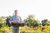 Portrait of gardener carrying crate with flower pots in garden
