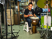 07 JUNE 2016 - BANGKOK, THAILAND: A drum seller plays a bongo style drum in his instrument shop in Verng Nakorn Kasem, also known as the Thieves' Market. Verng Nakorn Kasem was one of Bangkok's most famous shopping districts. It is located on the north edge of Bangkok's Chinatown, it grew into Bangkok's district for buying and selling musical instruments. The family that owned the land recently sold it and the new owners want to redevelop the famous area and turn it into a shopping mall. The new owners have started evicting existing lease holders and many of the shops have closed. The remaining shops expect to be evicted by the end of 2016.   Bangkok's Chinatown, considered by some to be one of the best preserved Chinatown districts in the world, is changing. Many of the old shophouses are being demolished and replaced by malls and condominium developments.        PHOTO BY JACK KURTZ