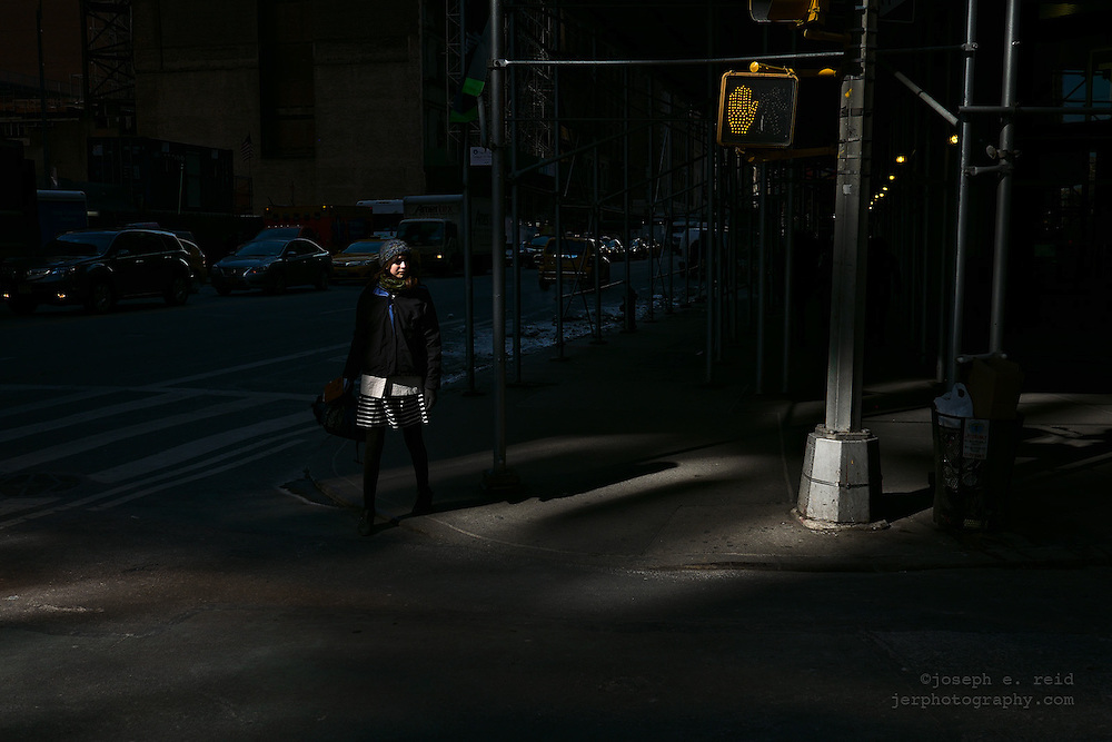 Woman waiting to cross Broadway at 5th St on cold winter day, New York, NY, US