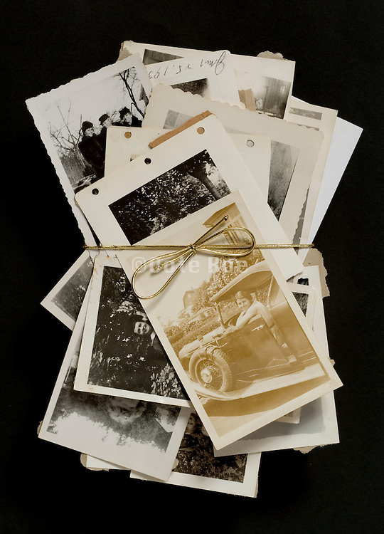 various old photographs hold together with a golden bow tie string