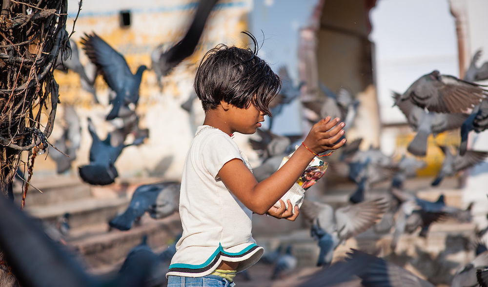 Girl playing with pigeons at Pushkar lake ghats (India)