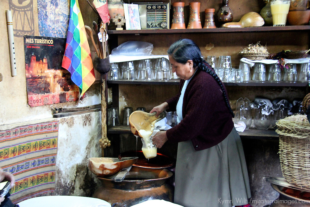 South America, Peru, Cusco. Peruvian woman  making traditional Chicha corn beer.